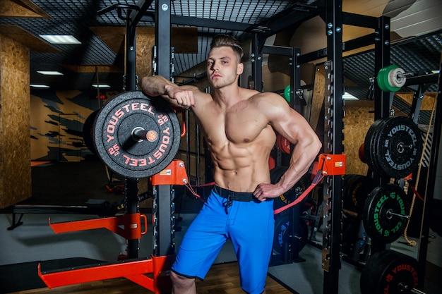 Seksowny mężczyzna na siłowni z hantlami