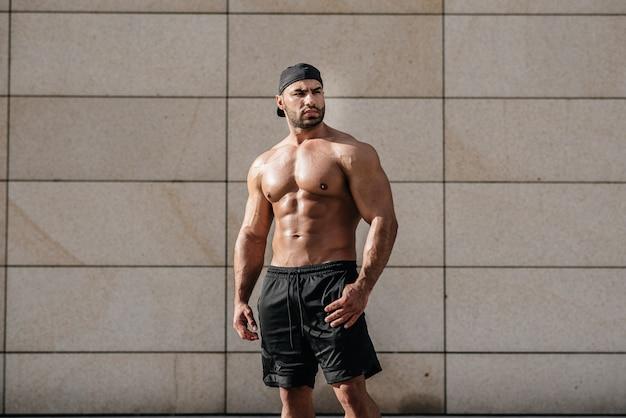 Seksowny mężczyzna pozuje toples w gorącym słońcu. zdatność. styl życia