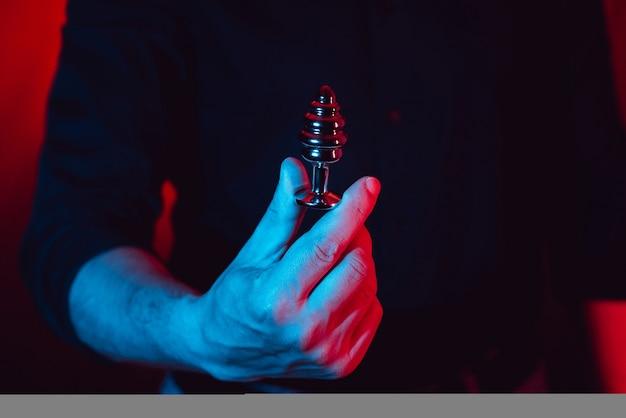 Seksowny mężczyzna trzyma w rękach korek analny bdsm. ten produkt jest przeznaczony tylko dla dorosłych