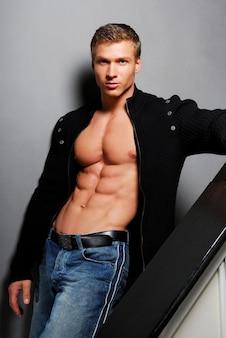 Seksowny młody człowiek z pięknym ciałem pozie w studio