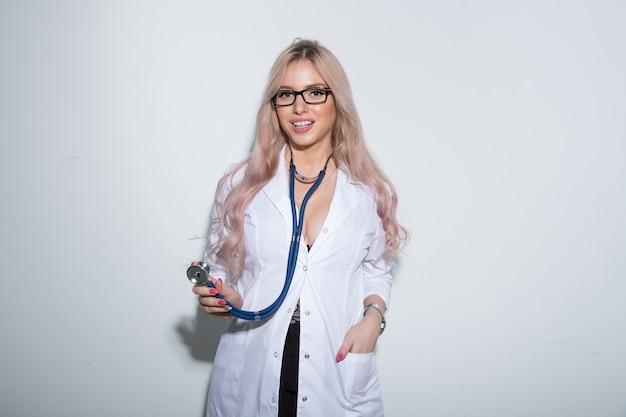 Seksowny młody lekarz w białej sukni medycznej na jasnym tle