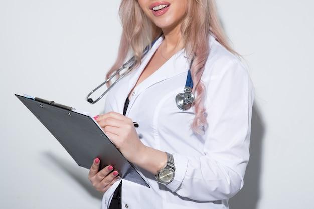 Seksowny młody lekarz w białej sukni medycznej pisze w karcie pacjenta