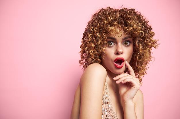 Seksowny model kręcone włosy czerwone usta zaskoczony wygląd studio moda ubrania różowe na białym tle