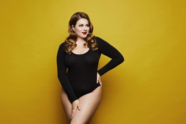 Seksowny model plus size, modna blondynka z jasnym makijażem, w czarnym body, ze stylową fryzurą, uśmiechnięta i pozująca
