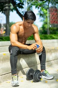 Seksowny muskularny mężczyzna siedzi trzyma butelkę do picia w pobliżu hantli podczas ćwiczeń na świeżym powietrzu w parku