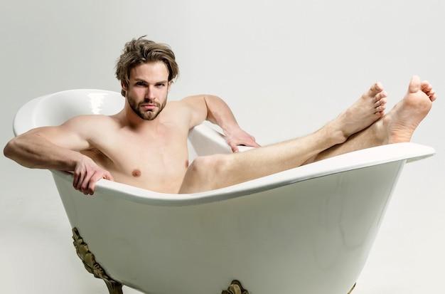 Seksowny nagi mężczyzna z nagim muskularnym tułowiem siedzi w wannie sportowy mężczyzna bierze kąpiel na białym tle na biały zmysłowy wesoły