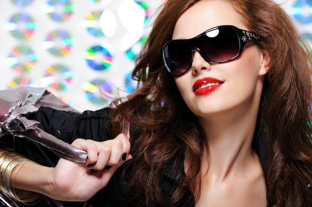 Seksowny piękna młoda kobieta z mody okulary i torebka