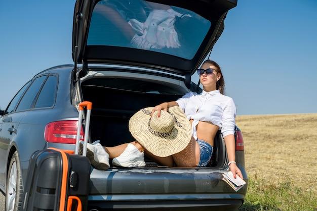 Seksowny piękny model europejski w letnie wakacje i okulary przeciwsłoneczne pozujące w luksusowym samochodzie w przyrodzie w letnim krajobrazie.