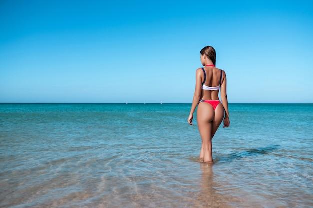 Seksowny plecy piękna kobieta w czerwonym bikini na dennym tle
