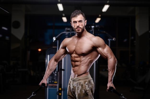 Seksowny silny kulturysta wysportowanych mężczyzn pompowania mięśni z hantlami