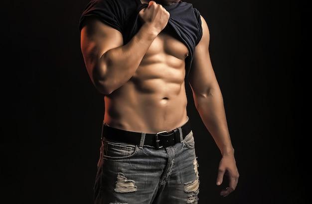 Seksowny silny młody człowiek z muskularnym ciałem w studio na czarnym tle.