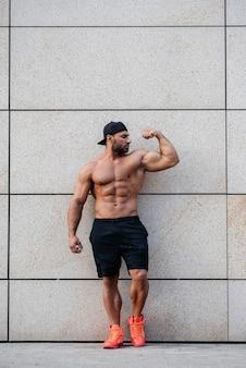 Seksowny sportowiec stoi topless przy ścianie. fitness, kulturystyka.