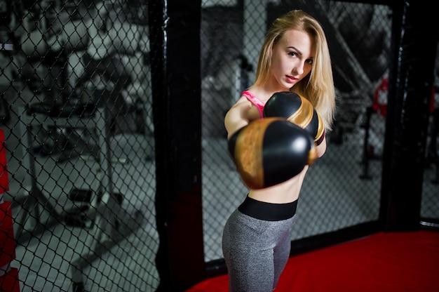 Seksowny sportowy blondynka bokser dziewczyna pozuje w ringu. dopasowany boks kobiet.