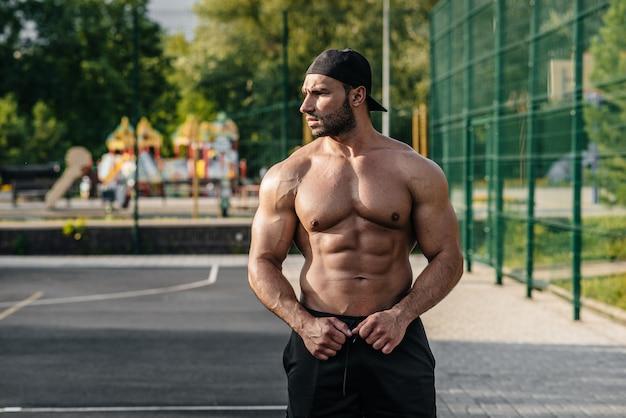 Seksowny sprawność fizyczna sportowiec pozuje na sporta pola toples. fitness, kulturystyka, zdrowy styl życia.