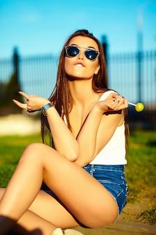 Seksowny stylowy model kobiety w lecie jasne tkaniny na ulicy