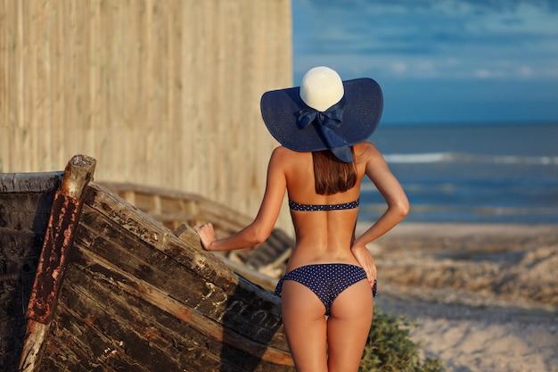 Seksowny tył pięknej kobiety pozuje w kolorowe stroje kąpielowe bikini na wybrzeżu morza. koncepcja podróży i wypoczynku w egzotycznym kraju. zgrabna sylwetka i seksowne ciało.