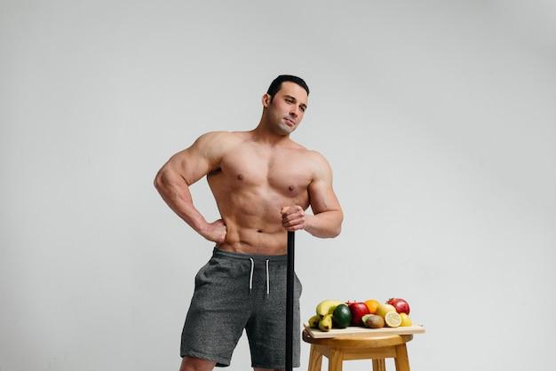 Seksowny wegański facet z nagim torsem pozuje w studio obok owoców. dieta. zdrowa dieta.
