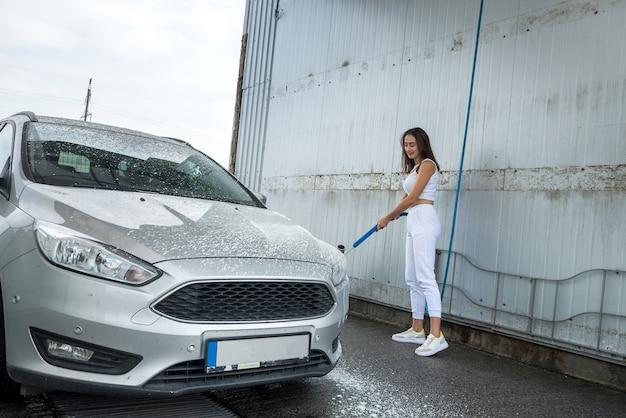 Seksualna młoda szczupła kobieta używa węża z pianką w sprayu do czyszczenia swojego samochodu z brudu. koncepcja czyszczenia