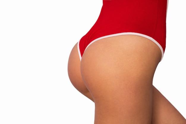 Seksualny okrągły tyłek w czerwonej bieliźnie na białym tle