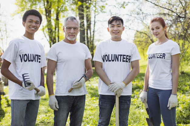 Sektor środowiska. energicznych czterech wolontariuszy stojących i trzymających narzędzia ogrodowe