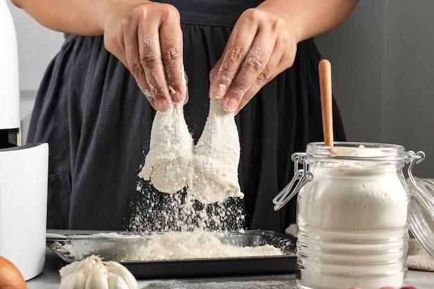 Selected focus kobieta domowy kucharz robi domowy chrupiący smażony kurczak, panierując kurczaki pałeczki mąką w kuchni
