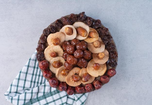 Selekcja suszonych owoców na talerzu na betonowej powierzchni.