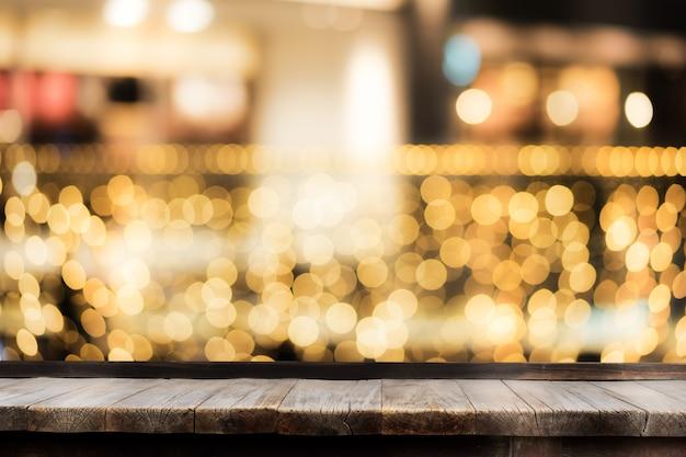 Selekcyjna ostrość drewniany stół przed dekoracyjnymi salowymi sznurkowymi światłami. boże narodzenie