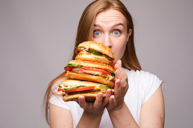 Selekcyjna ostrość dużych smacznych hamburgerów w rękach zdumionej dziewczyny