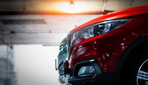 Selekcyjna ostrość na czerwonym błyszczącym suv sportowym samochodzie parkującym przy centrum handlowego krytym parkingiem. światła reflektorów o eleganckim i luksusowym wyglądzie. przemysł motoryzacyjny i koncepcja samochodu hybrydowego. parking podziemny.