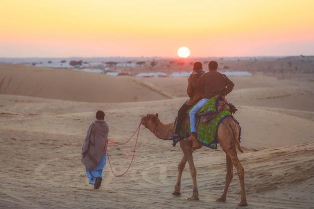 Selekcyjna ostrość na turystach jedzie wielbłąda na thar pustyni w jaisalmer podczas zmierzchu, india.