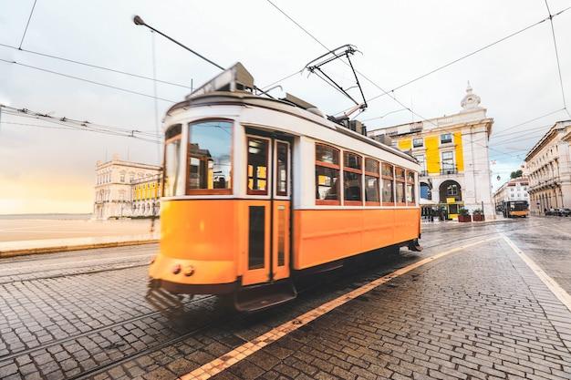 Selekcyjna ostrość na żółtym budynku z zamazanym starym tradycyjnym tramwajowym przelotnym bycity centrum lisbon, portugalia.