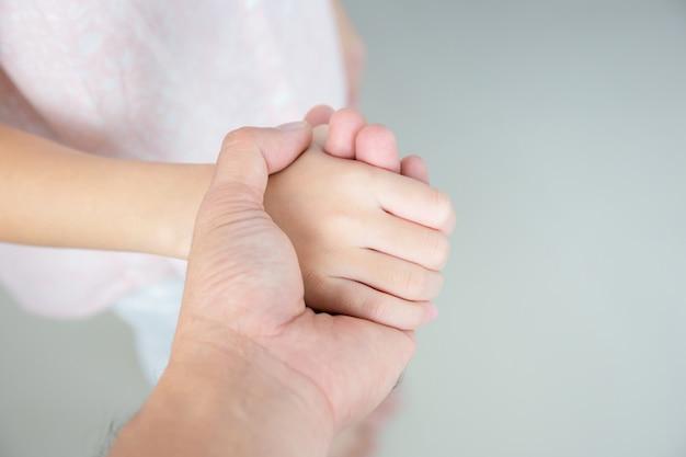 Selekcyjna ostrość ojciec i córka trzyma ręka w rękę