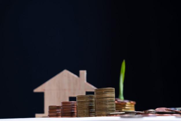 Selekcyjna ostrość pieniądze monety sterta z zamazanym domu modelem i ciemnym tłem