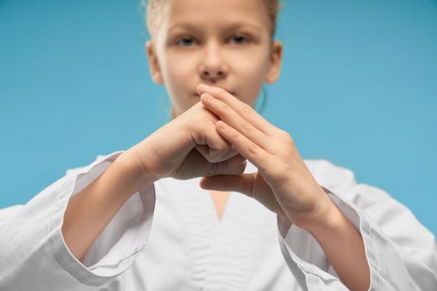 Selekcyjna ostrość ręki pokazuje pięść w studiu dziewczyna