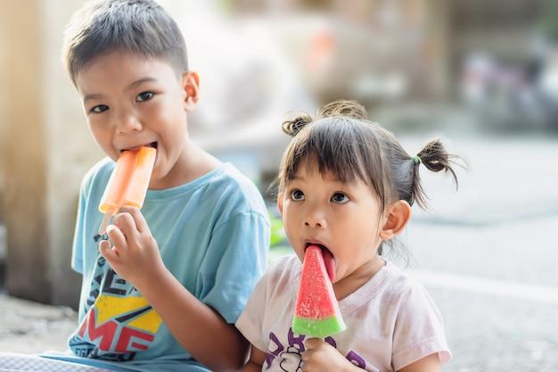 Selekcyjna ostrość u szczęśliwej azjatyckiej dziewczynki i jej brata jedzących różowe lody waniliowe. sezon letni,