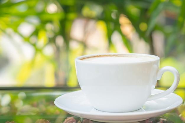Selekcyjna ostrości gorąca latte sztuki kawa w białej filiżance z metal łyżki zieleni zamazanym tłem