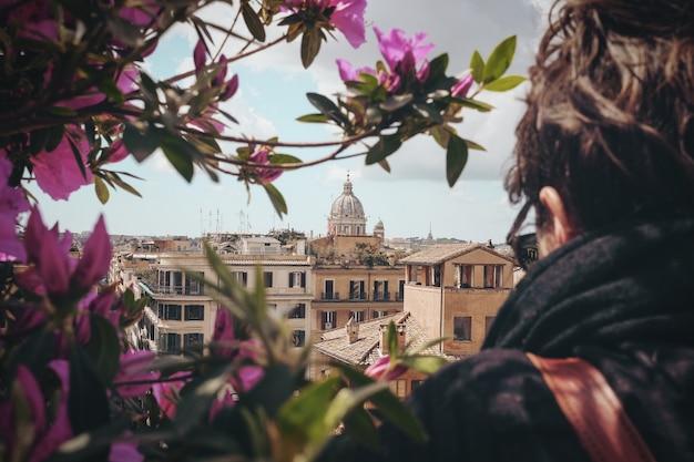 Selektywna fotografia ostrości człowieka stojącego przed betonowym budynkiem podczas dayitme