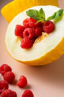 Selektywna ostrość. połączenie smaku świeżych dojrzałych owoców, melona i maliny na miękkim różowym tle