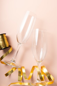 Selektywna ostrość. przezroczyste wysokie kieliszki do szampana, ze świąteczną złotą wstążką na miękkim różowym tle