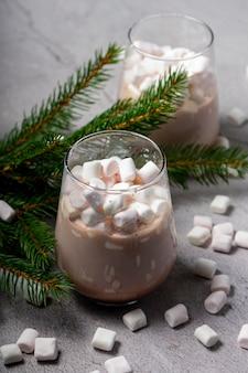 Selektywna ostrość. świąteczny napój. czekoladowe kakao z małymi białymi piankami z gałęziami drzew