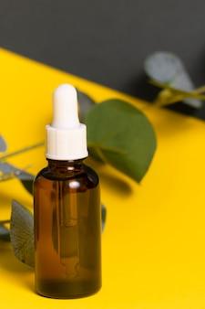 Selektywna ostrość. szklany słoik z pipetą. wewnątrz znajduje się kosmetyczny olejek organiczny do skóry twarzy i ciała. na żółto-szarym tle papieru. copyspace