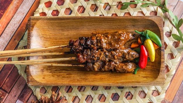 Selektywne focus - satay z kurczaka z grilla podawany na drewnianym talerzu