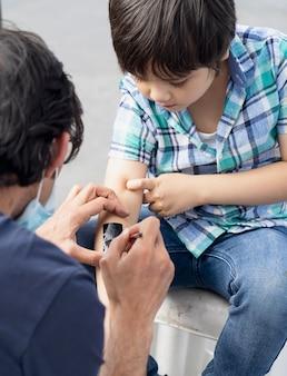 Selektywne fokus dziecko robi tatuaż na ramieniu na imprezie. przycięte ujęcie przedstawiające proces nakładania tymczasowego tatuażu na ramię chłopca. dziecko bawi się zabawą po zamknięciu,