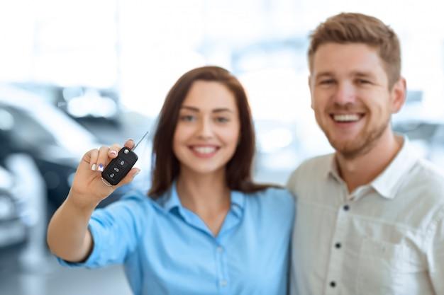 Selektywne fokus na kluczyk samochodowy piękna szczęśliwa kobieta trzyma przytulanie z przystojnym mężem w salonie samochodowym
