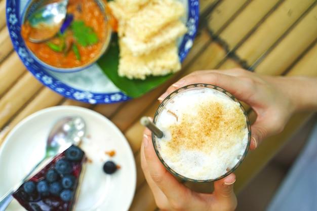 Selektywne fokus ręce kobiety trzyma szklankę mrożonej tajskiej pomarańczowej herbaty mlecznej ze świeżego mleka i świeżo deserów
