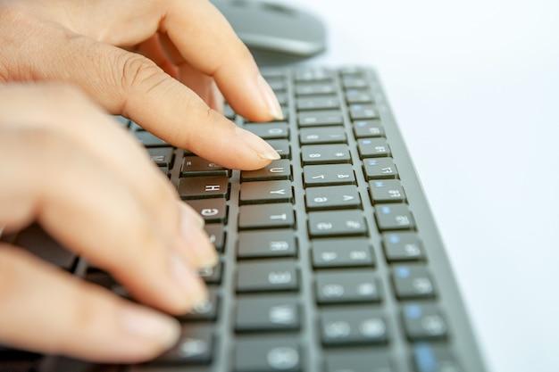 Selektywne fokus, ręka kobiety pracującej w domowym biurze na nowoczesnej klawiaturze.