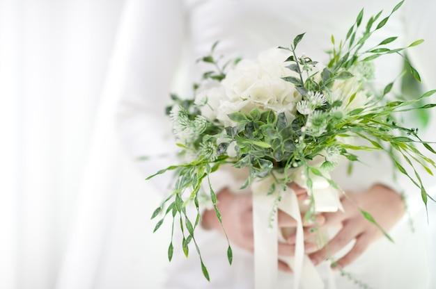 Selektywne fokus ręka panny młodej trzyma bukiet ślubny białe i zielone odcienie. elegancka prostota szczęśliwego dnia.