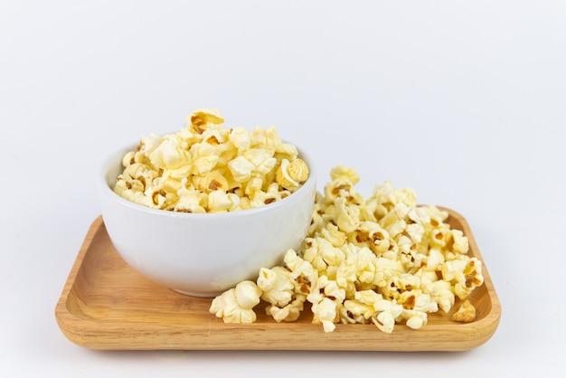 Selektywne fokus solony popcorn lub popcorn w białej misce i sterty na drewnianej tacy z białym tłem. popcorn to przekąska lub deser. popcorn z lato.