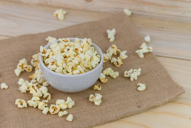 Selektywne fokus solony popcorn lub popcorn w białej misce na worku z drewnianym tłem. popcorn to przekąska lub deser. popcorn z lato.