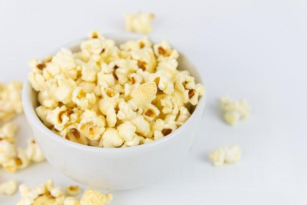 Selektywne fokus solony popcorn lub popcorn w białym bowl na białym tle. popcorn to przekąska lub deser. popcorn z lato.